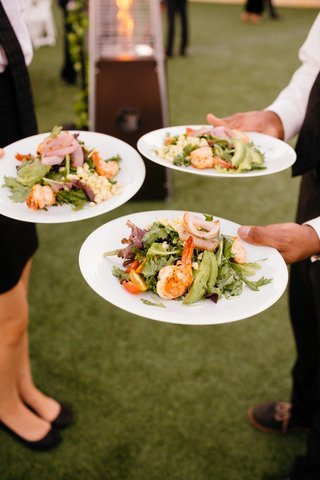 grilled-shrimp-salad-with-lettuce-servers-holding-plates