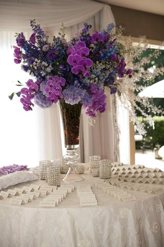 white-embroidered-linen-table-with-purple-flower-arrangement