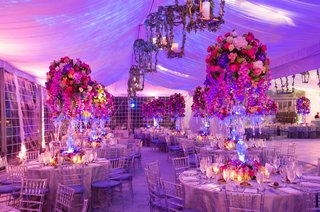 wedding-reception-tent-with-purple-lighting-and-lantern-frames-wrapped-in-greenery-hold-candles