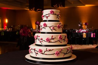 white-round-wedding-cake-with-cherry-blossom-design-and-black-ribbon-details