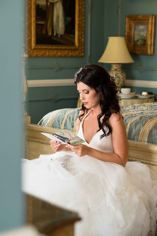 a-bride-in-her-wedding-gown-reads-a-card-before-the-ceremony