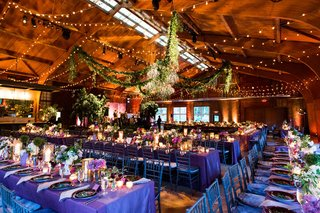 wedding-reception-barn-purple-linens-low-centerpieces-pink-purple-candles-twinkle-lights-garlands