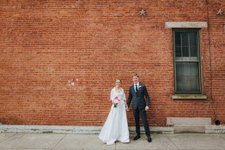 bride-in-a-line-wedding-dress-holds-hands-with-groom-in-grey-suit-in-front-of-brick-wall