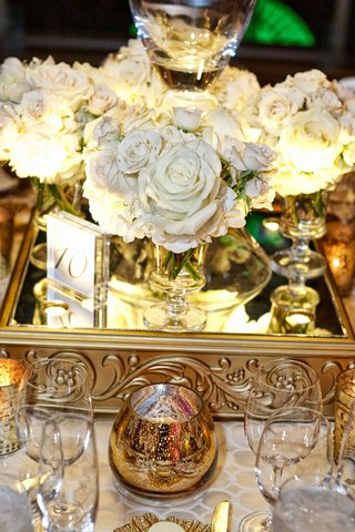 white-flowers-mirrored-stand-with-gold-detailing-and-glass-table-number-small-candle