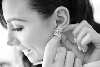 black-and-white-photo-of-bride-securing-chanel-logo-earrings