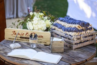 ranch-wedding-reception-with-wood-crate-of-beige-and-purple-scarf-blanket-on-rustic-wood-table