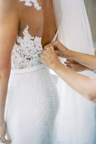 mother-of-bride-helping-daughter-button-wedding-dress-pronovias-lace-form-fitting-design-illusion