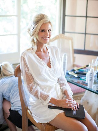 a-bride-in-a-white-robe-smiling-in-the-makeup-chair-after-getting-her-face-done