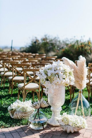 wedding-ceremony-at-terranea-with-white-orchid-hydrangea-protea-botanicals-feathers-in-glass-vase