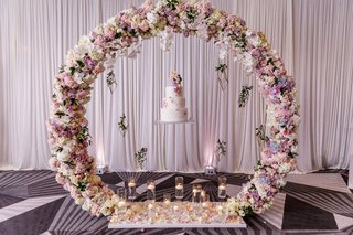 wedding-cake-floating-circle-of-flowers-wreath-candles-at-base-drapery-wedding-ideas-unique-display
