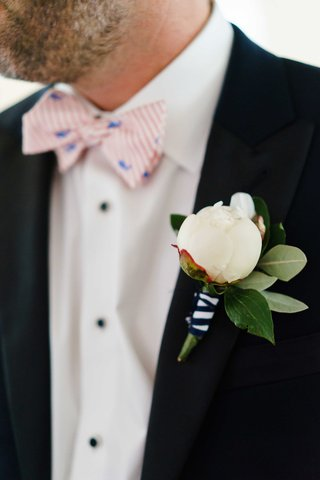 groom-with-striped-pink-and-white-bow-tie-and-blue-whale-with-white-peony-boutonniere-black-white