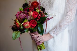 bride-holding-big-bouquet-with-protea-and-red-flowers