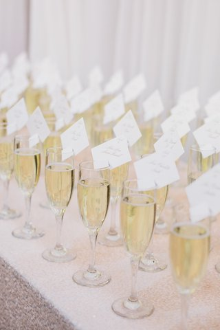 escort-cards-place-settings-on-champagne-flutes-filled-with-bubbly