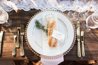 french-baguette-with-place-card-on-top-of-wedding-menu-and-rosemary-wood-table-lace-runner-gold