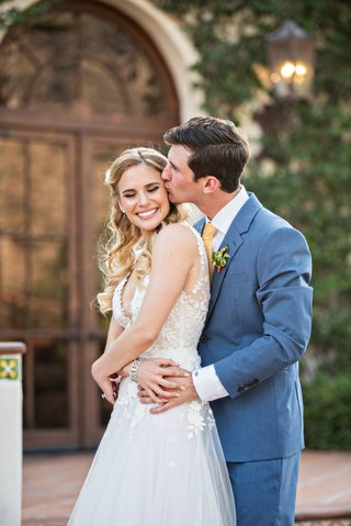 bride-in-mira-zwiliinger-wedding-dress-long-blonde-hair-groom-kiss-on-cheek-blue-suit-yellow-tie