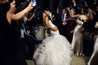 bride-and-groom-kiss-before-getting-into-limo-wedding-car-glow-sticks-guests-night-reception