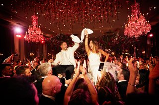 wedding-reception-bride-and-groom-on-chairs-with-guests-at-reception-chandelier-red-lighting