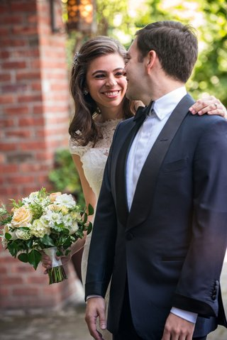 groom-in-navy-blue-tuxedo-with-black-lapels-and-bride-in-lace-wedding-dress-bouquet-first-look
