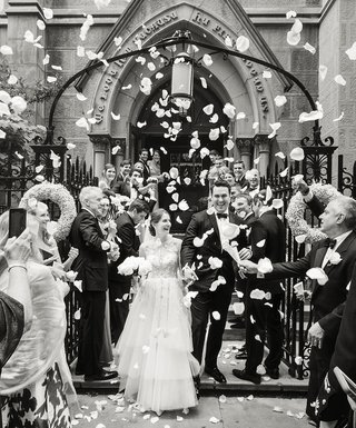 a-couple-exits-their-ceremony-at-st-thomas-mores-church-followed-by-an-ocean-of-rose-petals-and-l