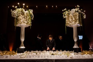 wedding-reception-escort-card-table-candles-flowers-tall-urns-with-lampshades-orchids-tulip-greenery
