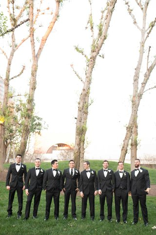 cute-men-in-tuxes-standing-in-green-grass