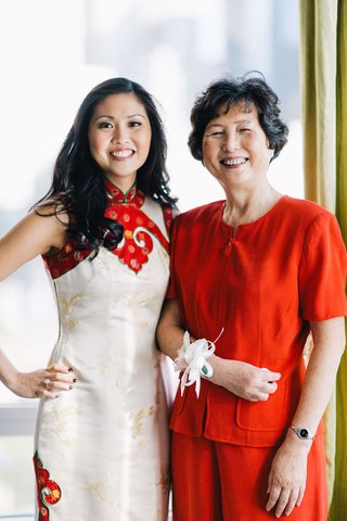 bride-in-a-white-qipao-with-gold-embroidery-red-trim-with-mother-in-a-red-outfit-and-white-corsage