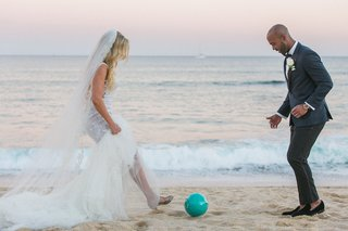 a-bride-and-groom-kick-a-soccer-ball-around-on-the-beach-after-their-wedding