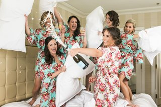 bride-sprays-champagne-while-bridesmaids-in-floral-robe-have-pillow-fight