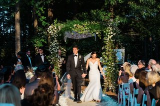 bride-and-groom-walk-back-up-aisle-holding-hands-green-chuppah-greenery-woods-outdoor-ceremony