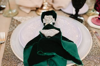 rock-used-as-place-card-on-top-of-forest-green-velvet-napkin