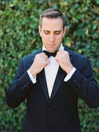 groom-in-a-black-tuxedo-tightening-up-his-black-bow-tie-outdoors