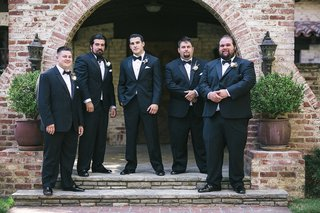 groom-and-groomsmen-in-black-tuxedos-white-rose-and-white-anemone-boutonnieres-at-hummingbird-nest