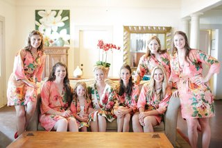 bride-bridesmaids-and-flower-girl-in-flower-print-pink-silk-robes-getting-ready
