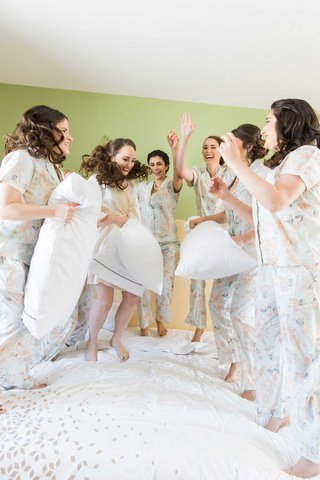 bride-bridesmaids-jump-on-bed-pillow-fight-wedding-florida-getting-ready-matching-pjs-outfits