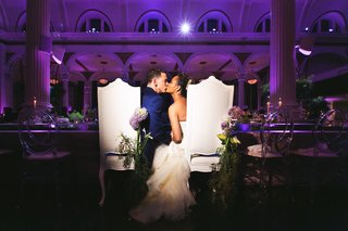bride-and-groom-kiss-at-tall-chairs-with-fresh-flowers-purple-lighting-kiss-reception