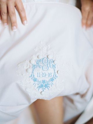 bride-pulling-up-dress-romona-keveza-with-something-blue-embroidery-wedding-dress-french-manicure