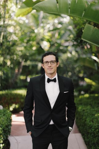 groom-in-tuxedo-and-glasses-tuxedo-white-pocket-square-hands-in-pockets-beverly-hills-hotel