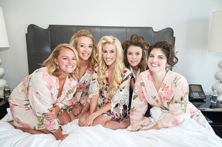bridesmaids-and-bride-on-bed-in-bridal-suite-wearing-pink-floral-robes