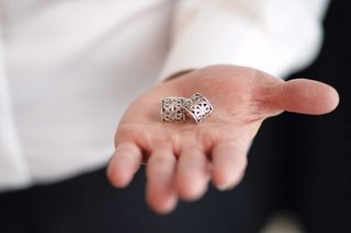 groom holding silver cuff links cufflinks in hand before wedding while getting ready