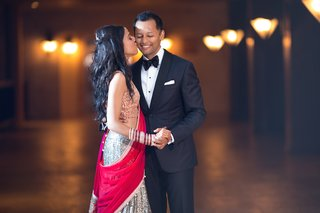 indian-bride-in-sari-with-gold-top-silver-skirt-and-fuchsia-wrap-kisses-groom-in-black-tuxedo