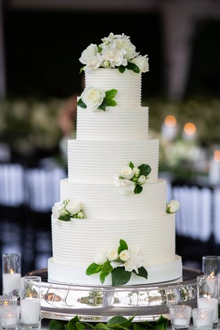 tall five layer wedding cake ribbed design fresh flowers and greenery silver display stand