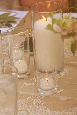 votive-candles-and-pillar-candle-in-hurricanes-on-lace-tablecloth-wedding