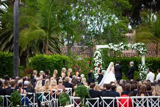 wedding ceremony white arch flowers greenery classic decor bridesmaids standing with  bouquets