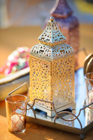 a-small-gold-lantern-with-a-unique-design-on-a-reflective-surface-next-to-small-low-candles