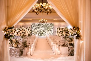 wedding ceremony in ballroom flower wall backdrop drapery at entrance the hidden garden