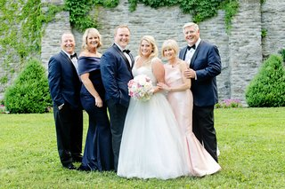 bride-and-groom-with-both-sets-of-parents-navy-blue-gown-for-mother-of-groom-and-light-pink-gown