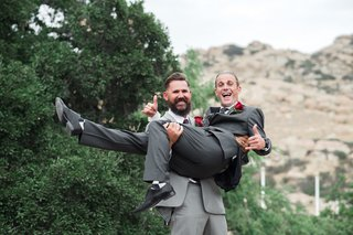 groomsman-in-light-grey-suit-picks-up-and-carries-groom-in-charcoal-grey-suit