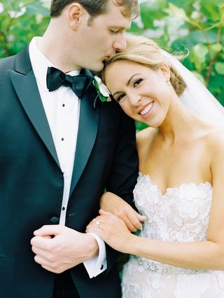 bride in mira zwillinger strapless wedding dress holding groom arm in tuxedo kissing top of head