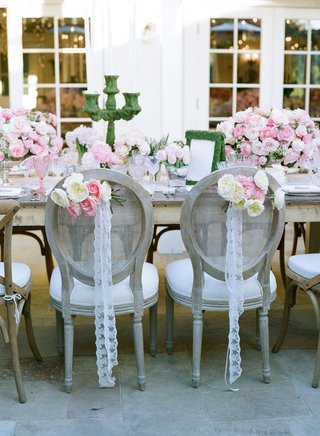lace-vintage-ribbon-and-white-pink-flowers-on-back-of-bride-and-groom-reception-chairs
