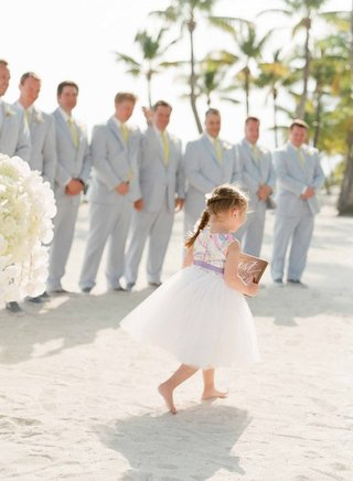 flower-girl-in-tulle-skirt-with-colorful-bodice-carries-sign-at-beach-wedding-ceremony